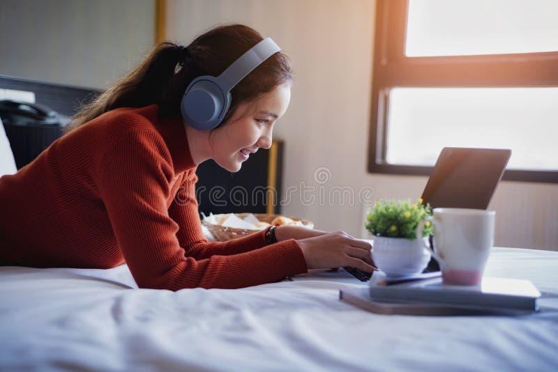 Jeune belle femme détendant avec des écouteurs d'utilisation écoutant la musique et l'ordinateur portable sur le lit pendant les  photos libres de droits
