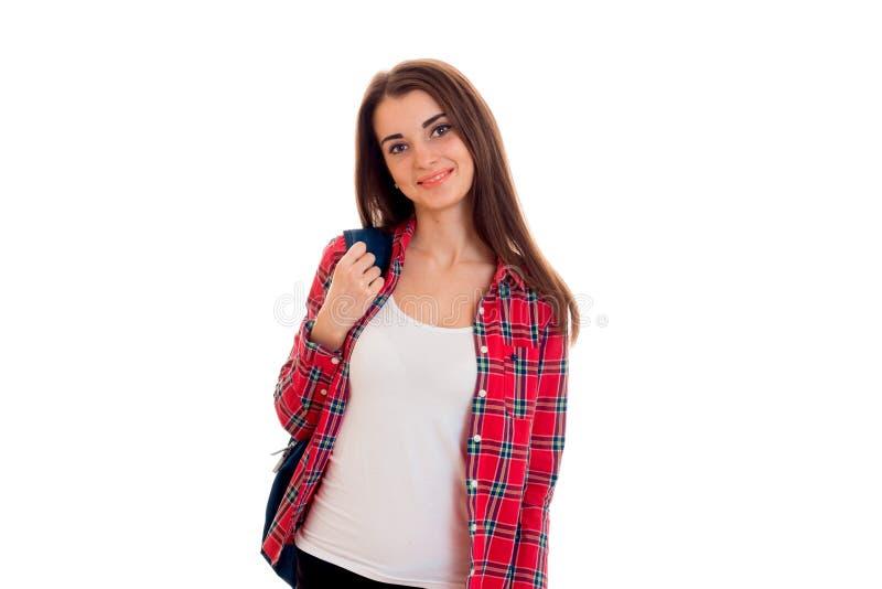 Jeune belle femme d'étudiant de brune avec le sac à dos bleu sur son épaule regardant l'appareil-photo et le sourire d'isolement  photos libres de droits