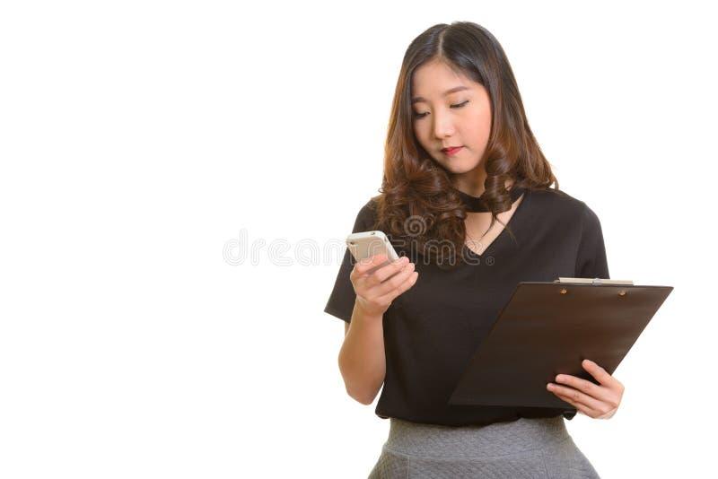 Jeune belle femme d'affaires asiatique à l'aide du téléphone portable tandis que HOL images stock