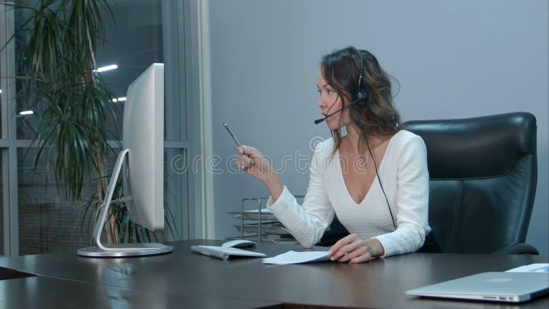 Jeune belle femme d'affaires asiatique avec le casque dans le bureau photographie stock