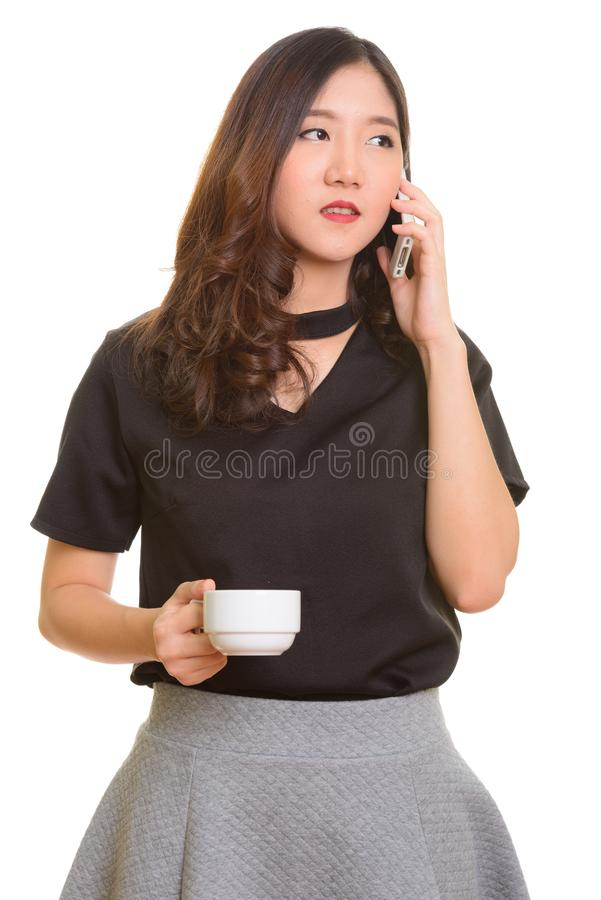 Jeune belle femme d'affaires asiatique parlant sur le whil de téléphone portable photos libres de droits