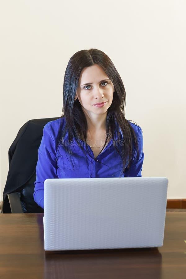 Jeune belle femme d'affaires dans le bureau travaillant sur l'ordinateur portable blanc photo stock