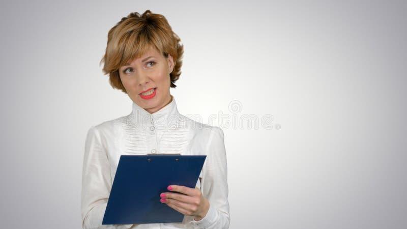 Jeune belle femme d'affaires dans un costume, souriant, heureux, travaillant avec un comprimé, écrivant un message sur le fond bl images libres de droits