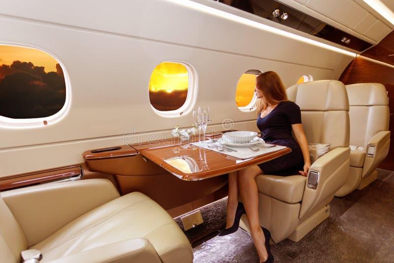 Jeune belle femme dans l'intérieur de luxe dans l'avion d'affaires image stock