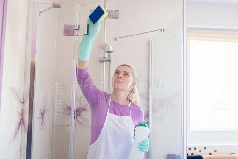 Jeune belle femme dans la carlingue blanche de douche de nettoyage de tablier photos libres de droits