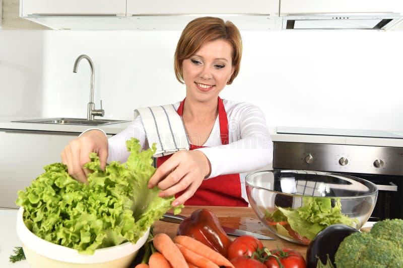 Jeune belle femme dans la cuisine rouge de tablier à la maison préparant le sourire végétal de saladier heureux image libre de droits