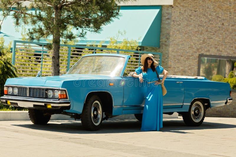 Jeune belle femme dans la longue robe azurée près d'une rétro voiture images stock