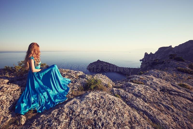 Jeune belle femme dans la robe bleue regardant à la mer de montagnes images stock
