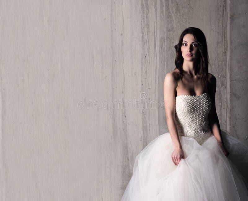 Jeune belle femme dans la robe de mariage près du mur en béton photos stock