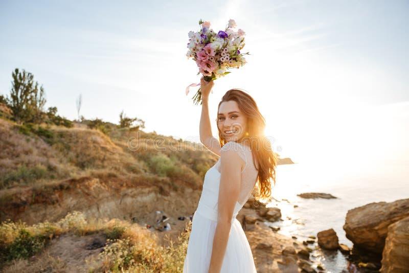 Jeune belle femme dans la robe de mariage sur la plage photo libre de droits