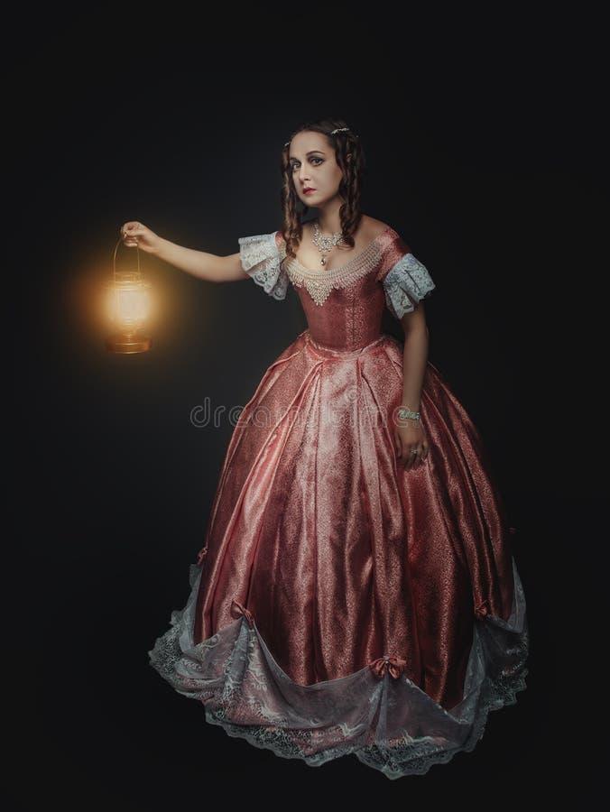 Jeune belle femme dans la robe médiévale avec la lampe sur le noir image stock