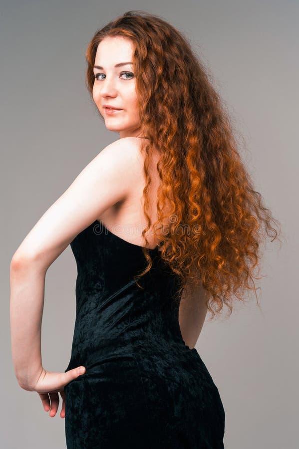 Jeune belle femme dans la robe noire avec le long remplaçant rouge de poils image stock