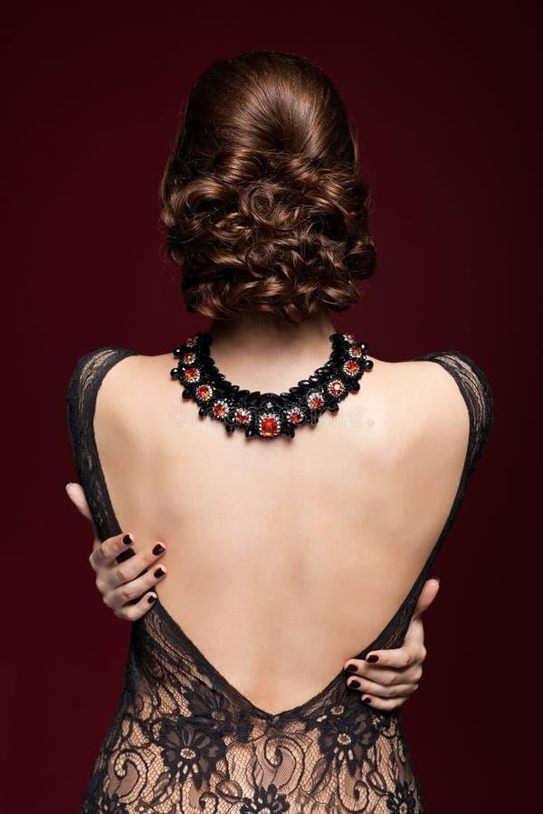 Jeune belle femme dans la robe noire de l'arrière sur le marsala c images libres de droits