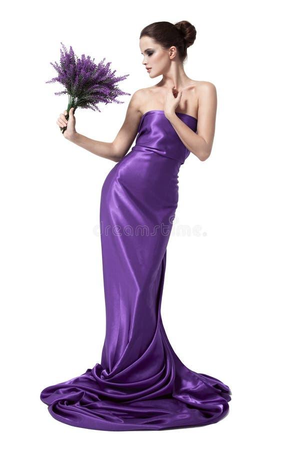 Jeune belle femme dans la robe pourpre avec la fleur images stock