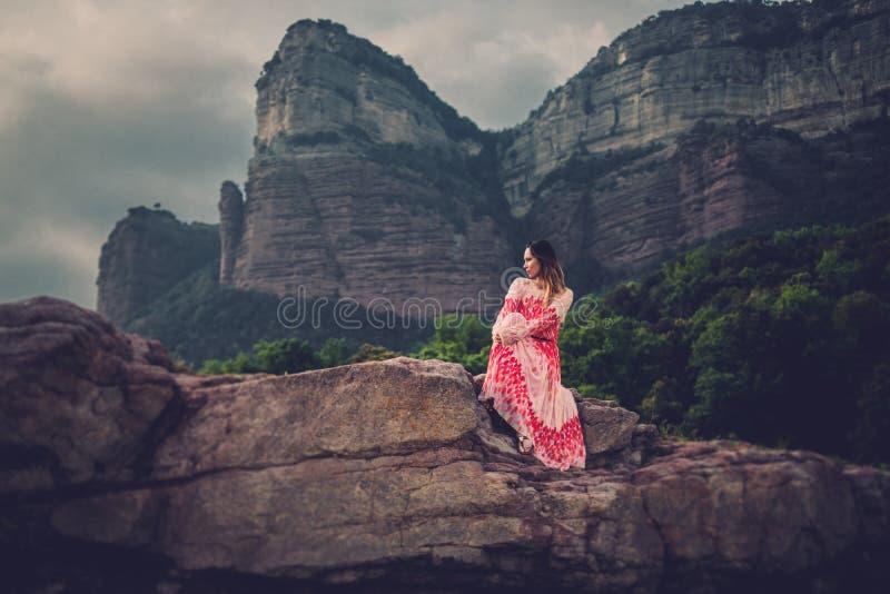 Jeune belle femme dans la robe rouge regardant sur des montagnes L'Espagne, Sant Roma de Sau photos stock