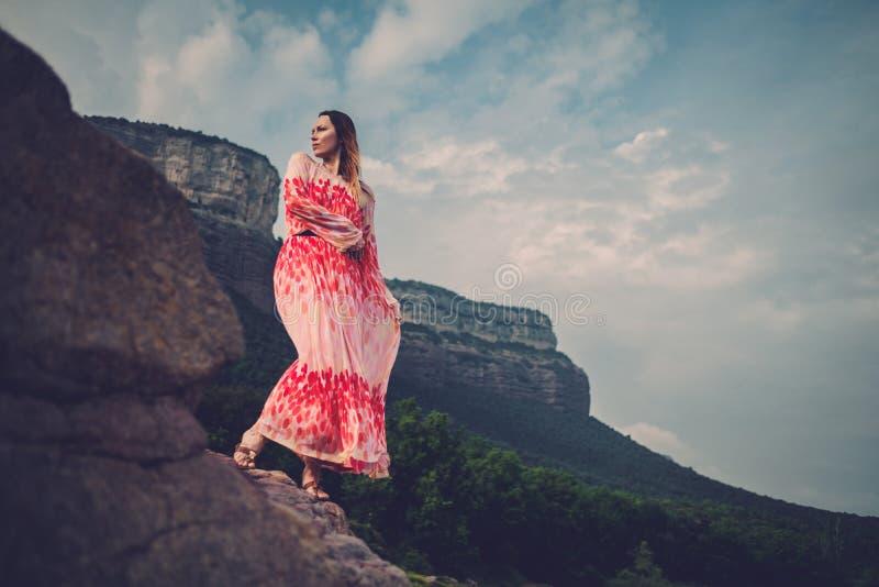 Jeune belle femme dans la robe rouge regardant sur des montagnes L'Espagne, Sant Roma de Sau images libres de droits