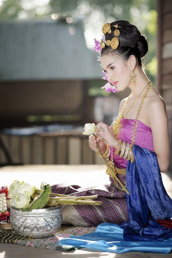 Jeune belle femme dans la robe traditionnelle thaïlandaise avec le flowe de lotus photos stock