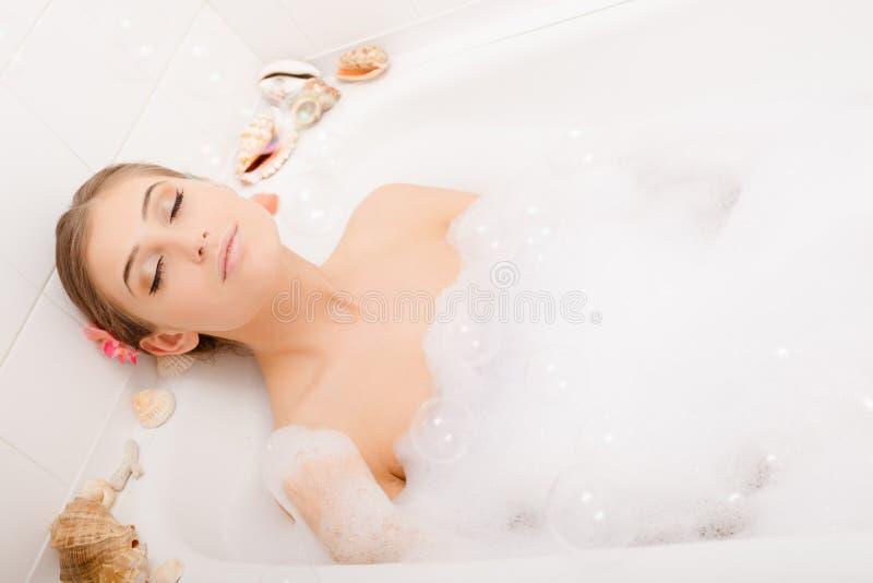 Jeune belle femme dans le bain de mousse images libres de droits