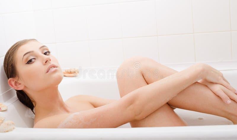 Jeune belle femme dans le bain de mousse photographie stock libre de droits
