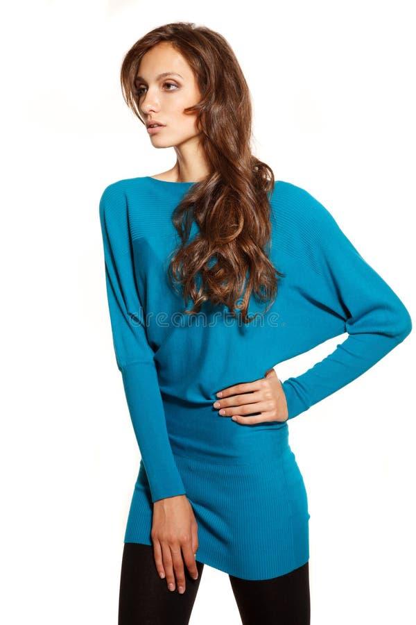 Jeune belle femme dans le chandail bleu sur le fond blanc images libres de droits