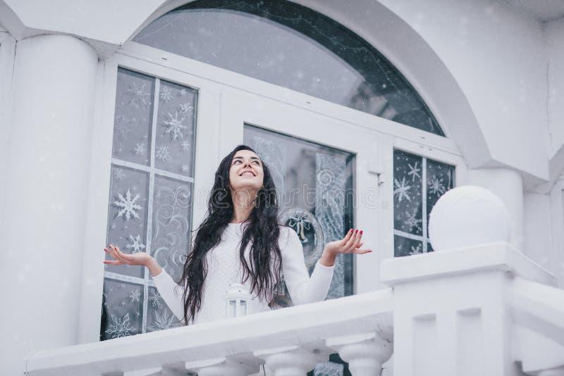 Jeune belle femme dans le chandail se tenant sous les chutes de neige image stock