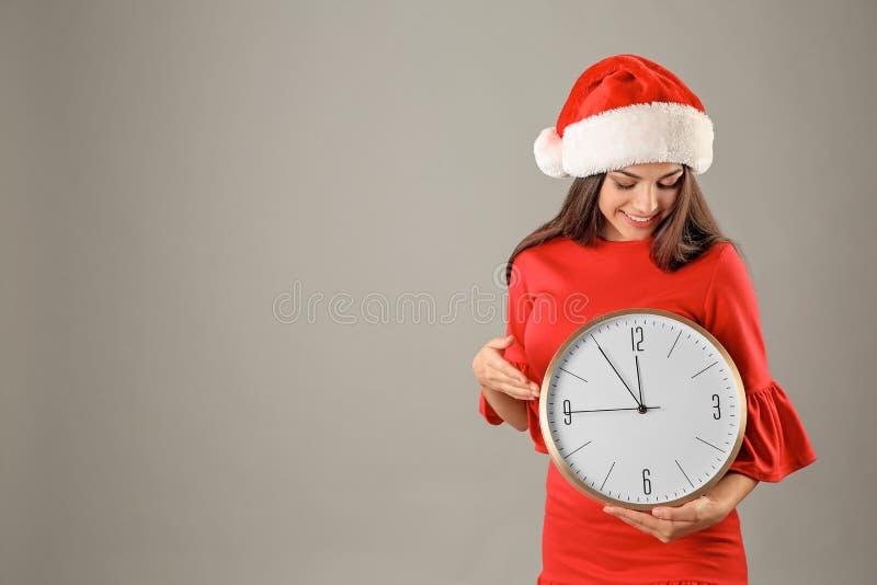 Jeune belle femme dans le chapeau de Santa tenant la grande horloge images libres de droits