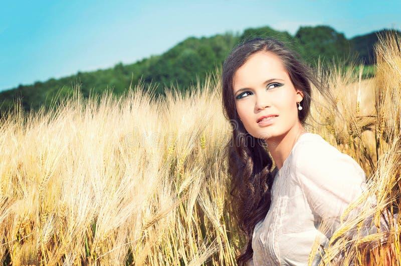 Jeune belle femme dans le domaine de blé d'or photos stock