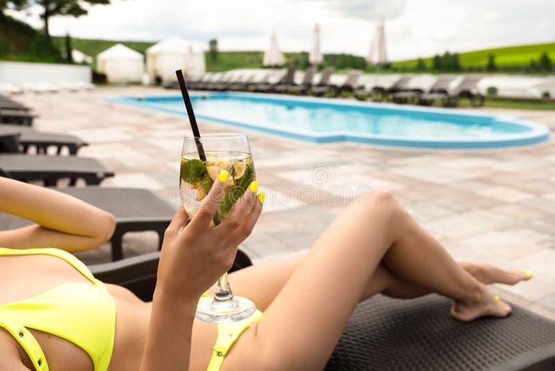 Jeune belle femme dans le maillot de bain jaune sexy se trouvant sur le fainéant se bronzant au cocktail potable de piscine d'hôt photographie stock libre de droits