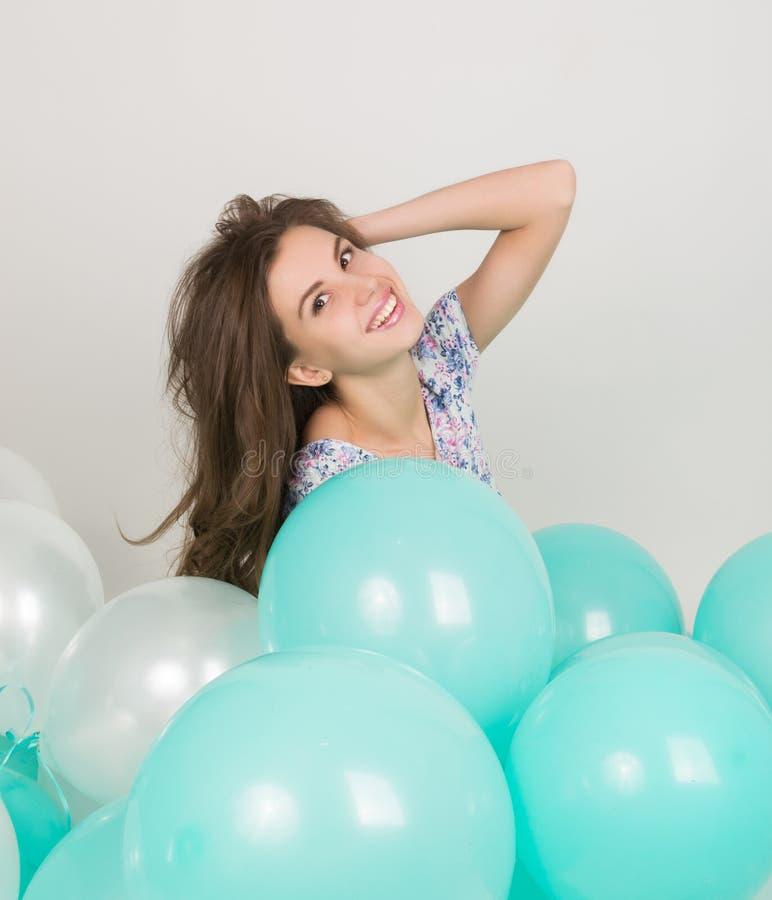 Jeune belle femme dans les shorts blancs et le dessus coloré jouant avec des ballons, mouvement lent photographie stock libre de droits
