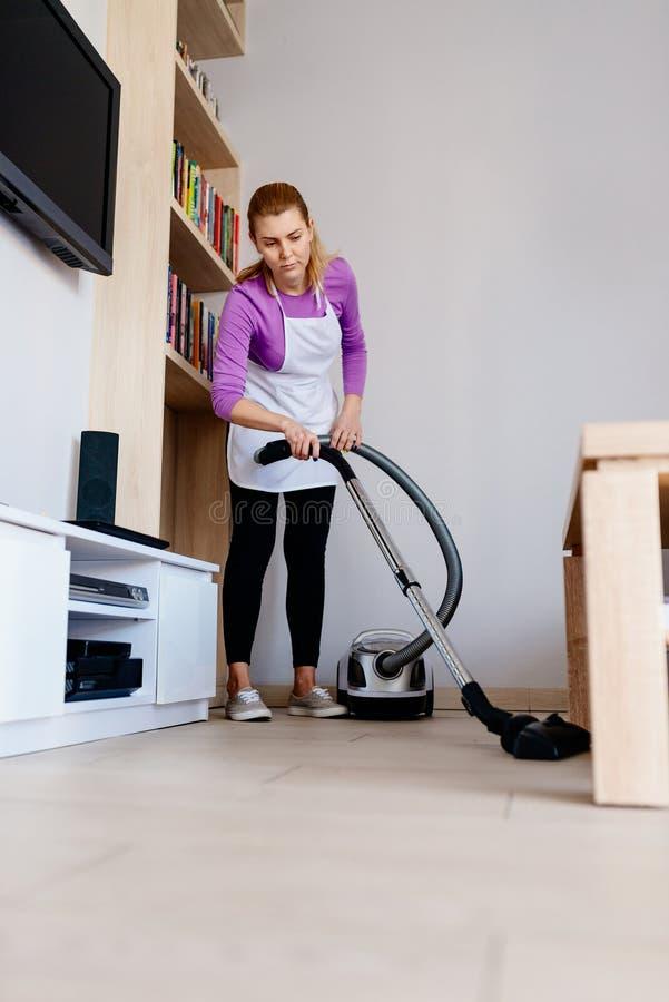 Jeune belle femme dans nettoyer à l'aspirateur blanc de tablier service de nettoyage images stock