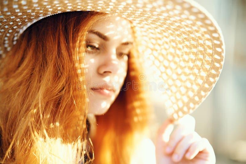 Jeune belle femme dans un chapeau au soleil, lumière, été photographie stock libre de droits