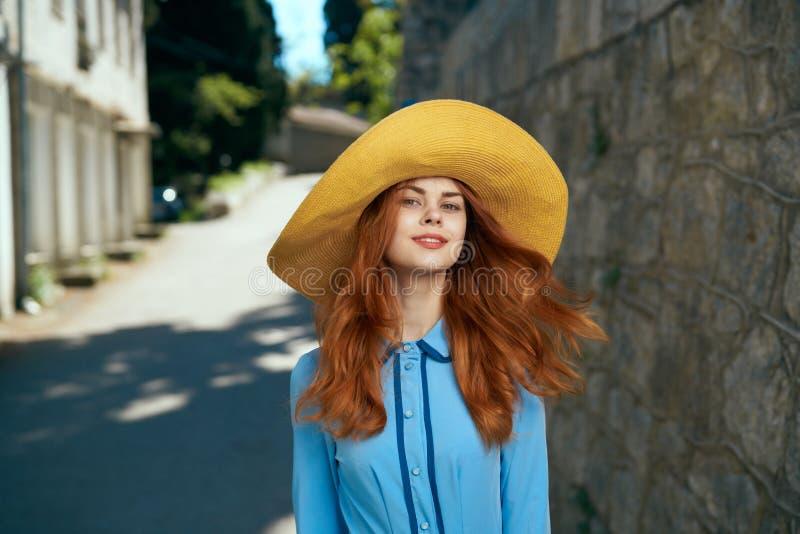 Jeune belle femme dans un chapeau dans une ruelle de ville d'été images stock