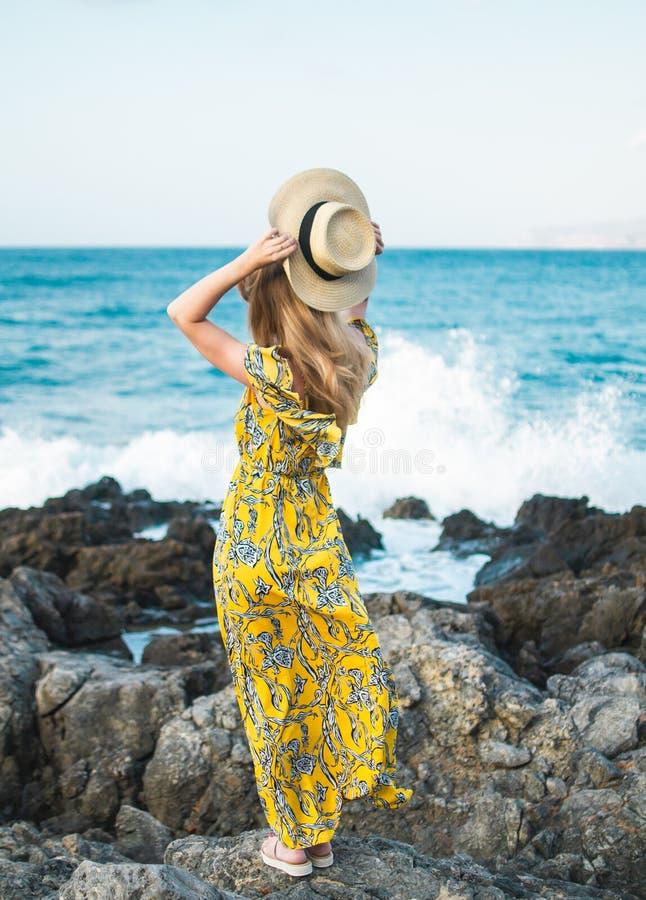 Jeune belle femme dans un chapeau et une maxi robe jaune, jour ensoleillé, concept de liberté, vacances photos libres de droits