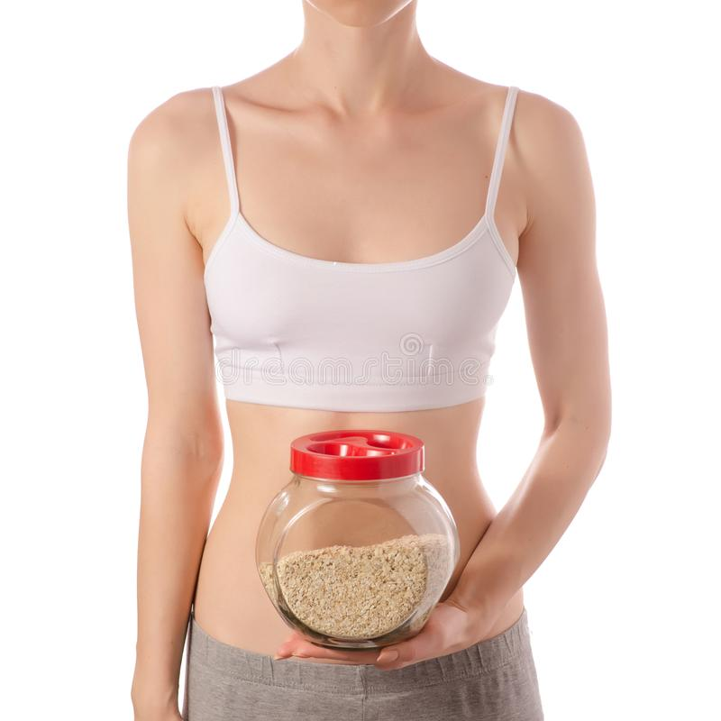 Jeune belle femme dans un dessus blanc de T-shirt dans le pot en verre de mains de beauté de gruau de farine d'avoine saine photos libres de droits