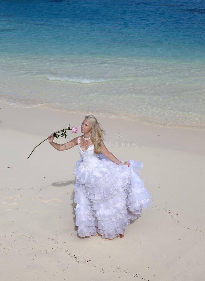 Jeune belle femme dans une longue robe blanche de jeune mariée sur le sable sur la plage par la mer bleue photo stock