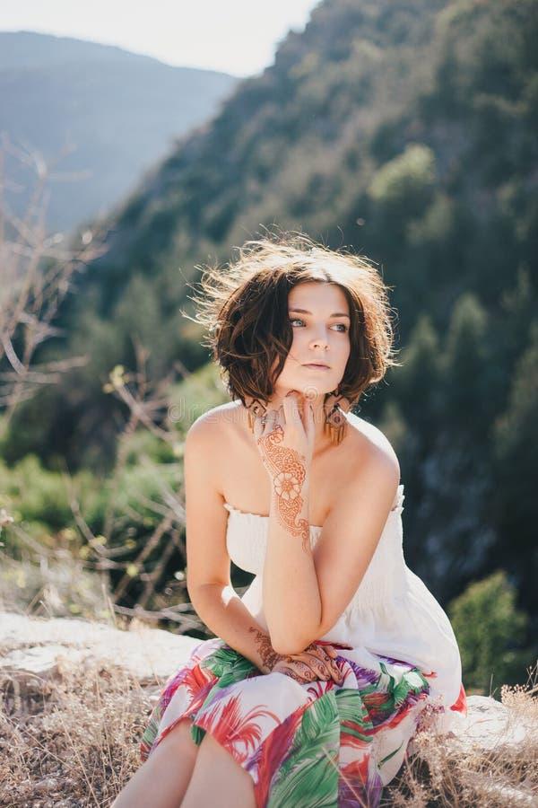 Jeune belle femme dans une robe moderne avec le mehendi posant parmi des montagnes photo libre de droits
