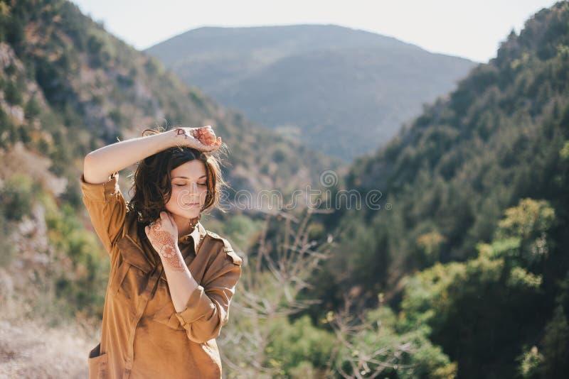 Jeune belle femme dans une robe moderne avec le mehendi posant parmi des montagnes photographie stock
