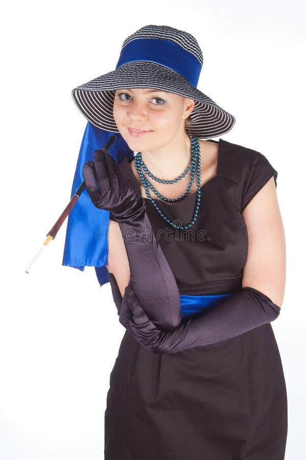 Jeune belle femme dans une robe pour des cocktails et un chapeau photo libre de droits