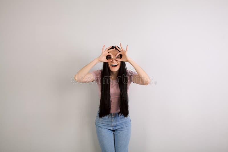 Jeune belle femme de brune avec de longs cheveux se tenant prêt le fond gris souriant avec sa bouche ouverte et la fabrication image libre de droits