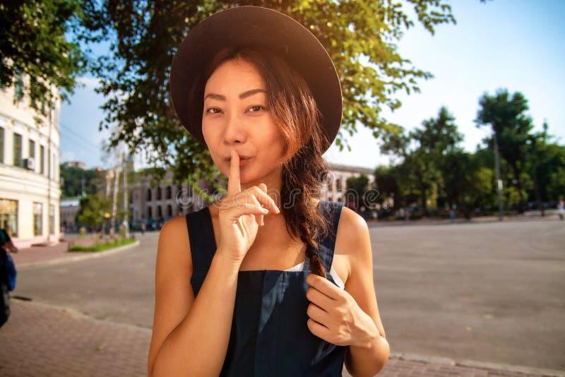 Jeune belle femme de brune montrant le signe de silence avec le doigt sur des l?vres dehors photo stock