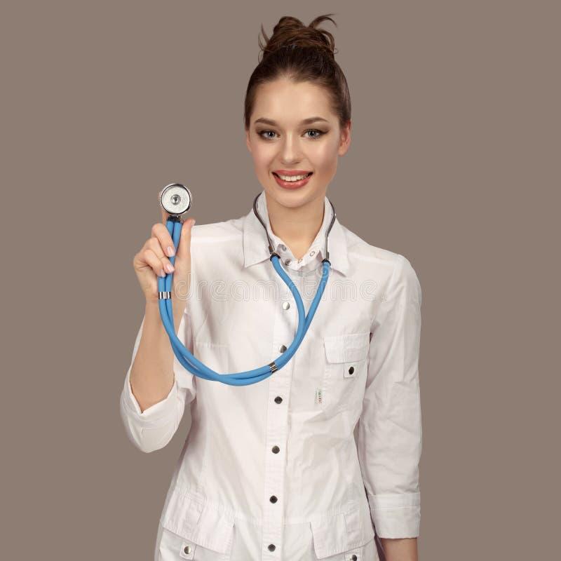 Jeune belle femme de docteur souriant au-dessus du fond gris Stéthoscope photographie stock libre de droits