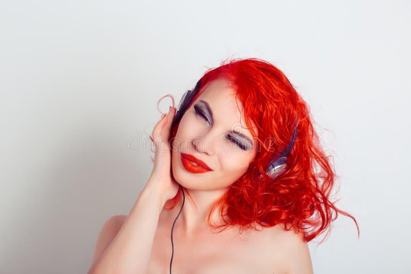 Jeune belle femme de fille détendant et écoutant la musique avec des écouteurs photos stock