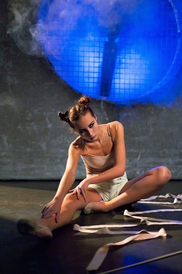 Jeune belle femme de gymnaste faisant étirant des exercices sur le plancher au gymnase images stock