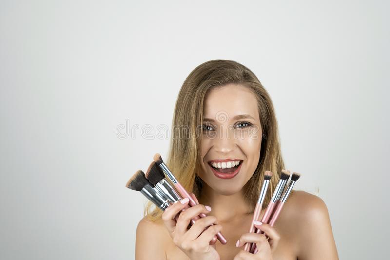 Jeune belle femme de sourire blonde tenant le fond blanc d'isolement par brosses roses photos libres de droits