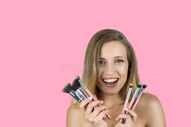 Jeune belle femme de sourire blonde tenant le fond rose d'isolement par brosses roses photo libre de droits