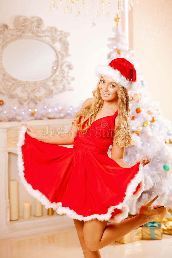 Jeune belle femme de sourire de Santa près de l'arbre de Noël Gir photographie stock libre de droits