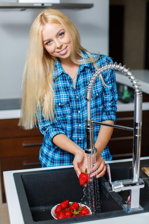 Jeune belle femme de sourire heureuse avec la fraise images stock