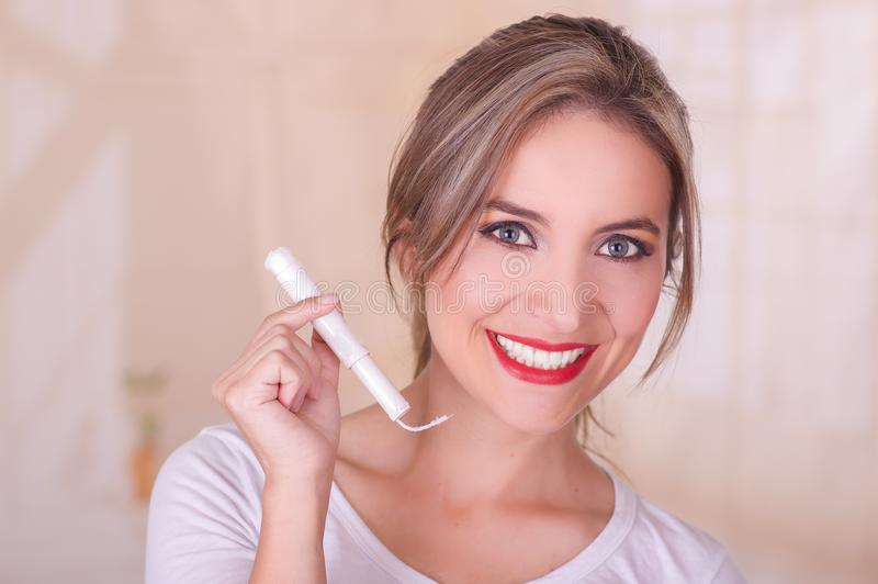 Jeune belle femme de sourire tenant un tampon de coton de règles dans sa main, à un arrière-plan brouillé images libres de droits