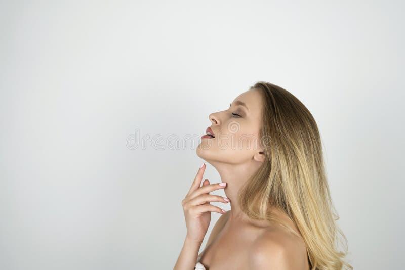 Jeune belle femme de sourire touchant son menton avec une fin de moitié-visage de position de main vers le haut de fond blanc d'i image stock