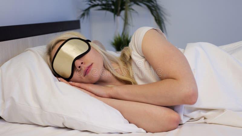 Jeune belle femme dormant dans le lit avec le masque d'oeil photos stock